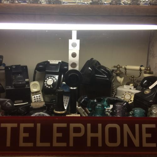 Vintage telephones in vintage telephone booth at Collectors' Corner Museum